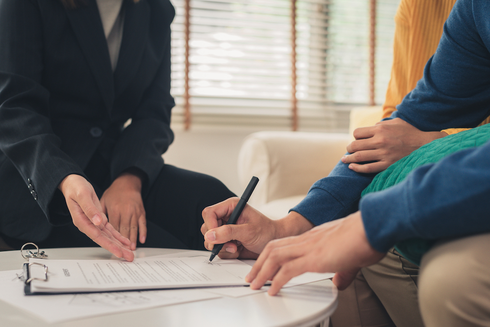 Happy young Asian couple and realtor agent. Cheerful young man signing some documents while sitting at desk together with his wife. Buying new house real estate. Signing good condition contract.